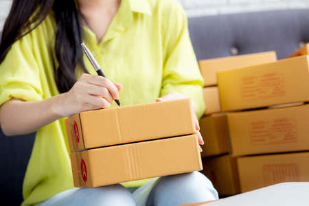 Closeup hand of young asian woman writing address on parcel box at home for delivery order to customer, shipping and logistic, merchant online and seller, business owner or SME, online shopping.