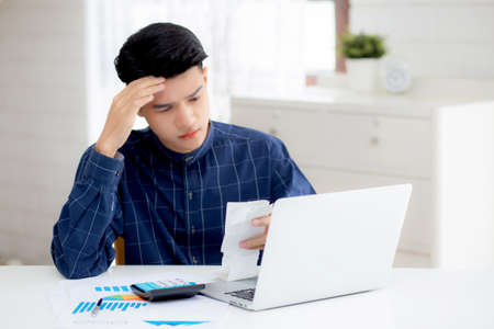Young asian man calculating expenses household about finance and frustrated on desk at home, male checking bill having stress and worried, debt and tax, expression and emotion, business concept.