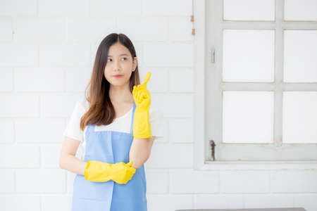 Portrait young asian woman is housekeeper in rubber gloves and apron for protection at home, uniform of maid, cleaning and washing, girl standing worker positive, one people, lifestyle concept.
