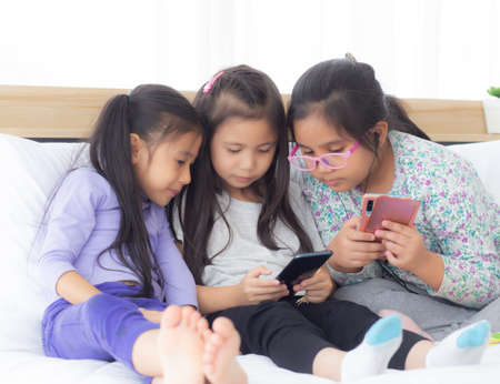 Happy asian little kid and friends playing smartphone on sofa at home, children using phone together on couch, girl watching smart phone for entertainment, lifestyle and communication concept. Stockfoto