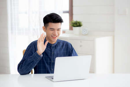 Young asian business man using laptop computer for video call online hello and communicate work from home, male conference with notebook and say hi, social distancing, communication concept. Archivio Fotografico