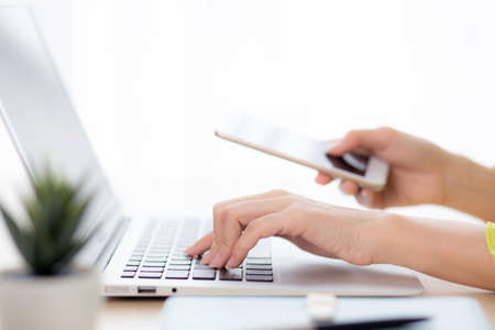 Closeup hand of young asian businesswoman working on laptop computer on desk at home office, freelance woman looking message on smart phone and typing on notebook, business and communication concept.