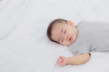 Portrait of asian little baby girl sleeping on bed in the bedroom at home, newborn napping with cozy and relax, infant innocence in bedtime, happy toddler cute, growth of child and emotion, indoors. Foto de archivo