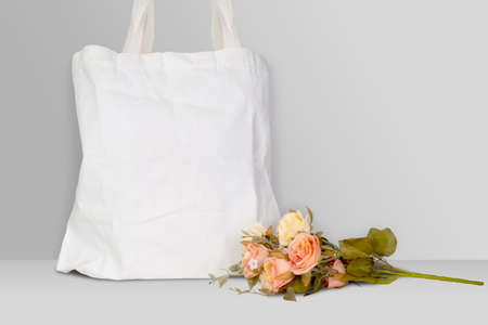 Mockup white tote bag fabric for shopping and flower on desk, mock up canvas bag textile with reusable.