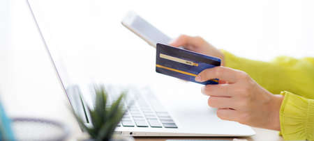 Closeup young asian business woman using smart phone and holding credit card while online shopping and payment with laptop computer on desk at home, female holding debit card, communication concept.