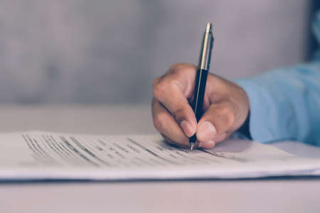 Hands of businessman signing contract about agreement for success on desk in the office, man signature document paperwork with pen, legal insurance and decision for deal, business concept.