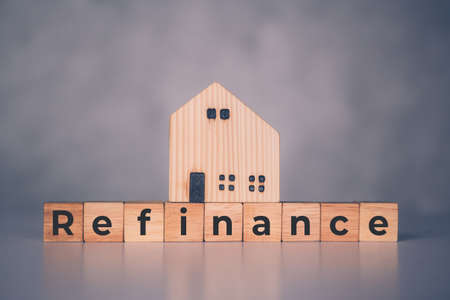 Wooden block with refinance word and house model about home and finance, loan and mortgage for real estate and property, residential and planning with budget, investment and earning, business concept.