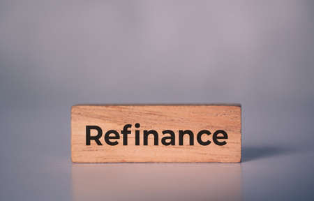 Wooden block with refinance word about home and finance, loan and mortgage for real estate and property, residential and planning with budget, nobody, investment and earning, business concept.