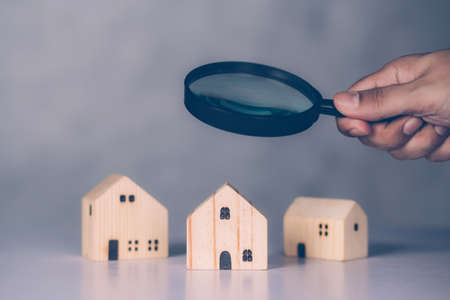 Hand of businessman hold magnifying glass looking house for examining and analyzing quality, inspection and choice home, purchase and search residential and investment, business and property concept.