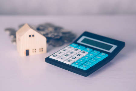 Investment about home with calculator and model house and coins on desk, property and real estate and mortgage, loan and finance, financial saving and account for residential, business concept.