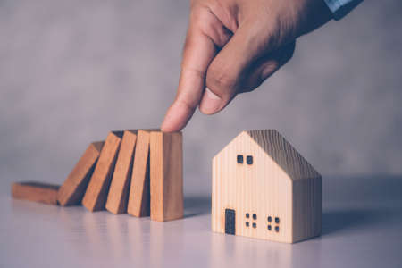 Hands of businessman stop risk about home with block wooden and safety, investment and insurance about real estate and property, planning and strategy, loan and debt of house, business concept.