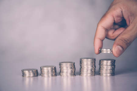 Hands of businessman put coin stack with increase growth, finance and saving, investment for profit and success, planning with financial, growing economy and fund, stock and income, business concept. Stok Fotoğraf