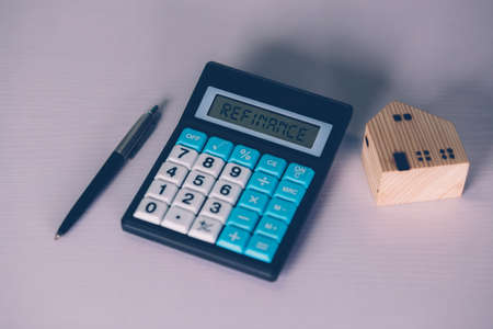 Calculator with text refinance home while expense for loan mortgage, investment and banking, property and cost, real estate and transfer for debt, planning and management of finance, business concept. Stok Fotoğraf