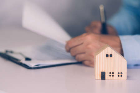 Real estate agent holding home and signing contract about agreement of real property on desk, house broker and planning investment, businessman writing on document form rent house, business concept. Stok Fotoğraf