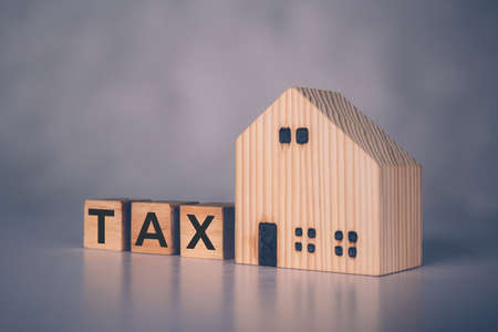 Wooden block cube with TAX word and home model, real estate and property about finance, planning with financial, investment about residential and tax, budget and taxation, business concept.