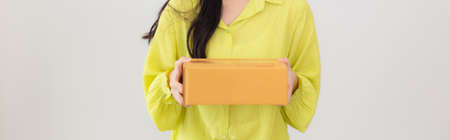 Young asian woman smiling and holding cardboard box at home, happy female carrying parcel box giving, present and gift, packaging for deliver, online shopping store and service concept.