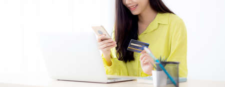 Young asian business woman using smart phone and holding credit card while online shopping and payment online with laptop computer on desk at home, female holding debit card, communication concept. Stok Fotoğraf
