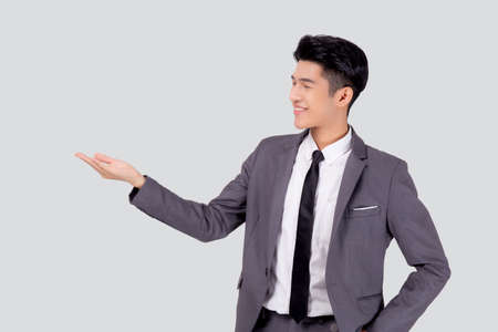 Portrait young asian business man in suit presenting isolated on white background, advertising and marketing, executive and manager, male confident showing success, expression and emotion.