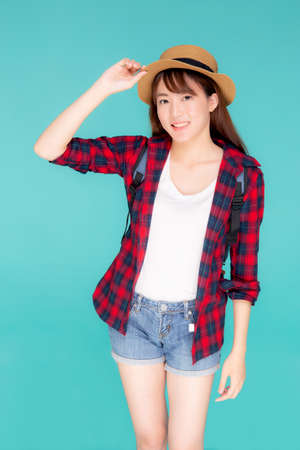Beautiful portrait young asian woman holding hat smile expression cheerful and enjoy travel summer trip holiday in vacation isolated blue background, tourist happy asia girl confident and excited. Stok Fotoğraf