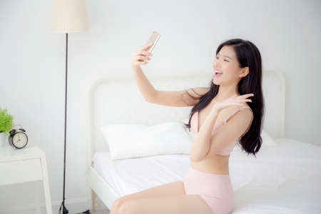 Beautiful young asian woman sexy in underwear talking a selfie on smartphone for social network in the bedroom, girl in lingerie relax with taking a picture on mobile phone on bed in the bedchamber.