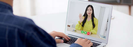 Young asian business man and woman video conference call online for discussion about statistics of finance with laptop computer, businesswoman explaining report with businessman, social distancing.