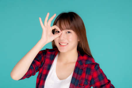 Beautiful happy young asian woman wear travel summer gesture ok sign with hand on eye having vision isolated on blue background, asia teenager girl expression with cheerful and fun while trip. Stok Fotoğraf
