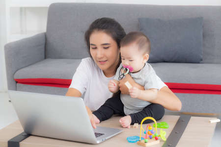 Young asian mother working on laptop computer while care daughter girl at home, mom and baby girl sitting using notebook video call, parent and bonding, indoors, family and business concept. Stok Fotoğraf