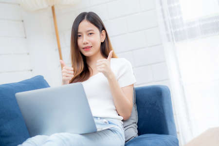 Young asian business woman smile and work from home with laptop computer online to internet on sofa in living room, freelance girl using notebook on couch with comfort, new normal, lifestyle concept.