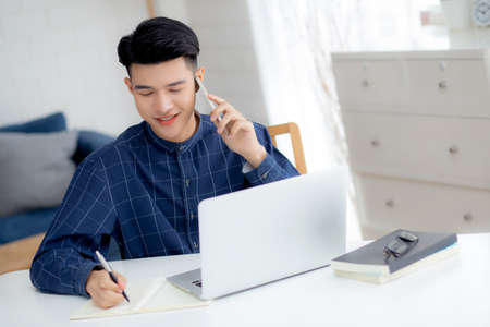 Young asian man talking phone and work from home with laptop computer, freelance male writing on notebook and speak on smartphone, stay home, domestic life, business and communication concept.