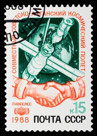 docking: USSR - CIRCA 1988: A stamp printed in USSR commemorates a Russian-Afghanistan space mission which included a Soyuz capsule docking at the Mir space station, circa 1988.