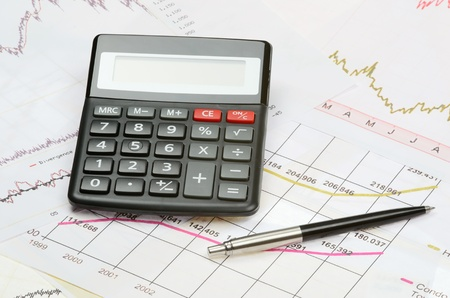 Black calculator and pen on a financial charts and graphs on the table photo