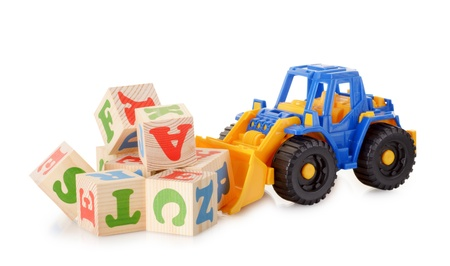 The wooden alphabet blocks with a toy tractor isolated on a white background Foto de archivo