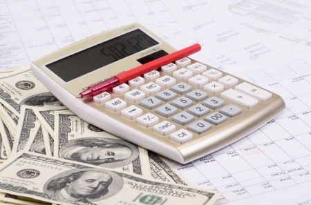 estimates: calculator with pen and dollars against estimates