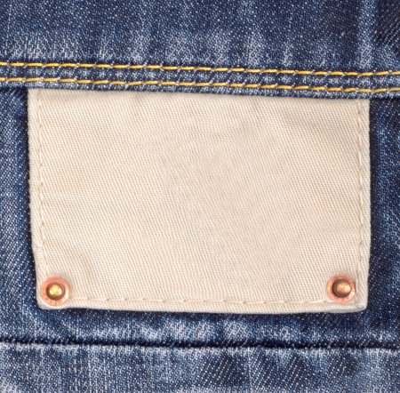 Blank cloth jeans label sewed on a blue jeans photo