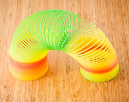 slinky: Slinky lying on the wooden background