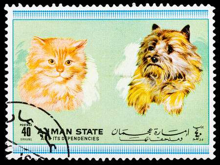 stamp collecting: AJMAN STATE - CIRCA 1974: A stamp printed in Ajman State shows Dogs and cats, series Pets, circa 1974