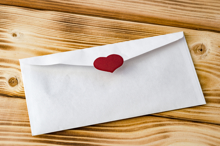Happy Valentines Day. Postal envelope with heart on a wooden background. Love. Celebratory background Stock Photo