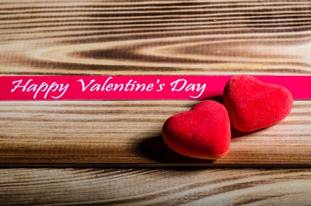 Happy Valentines Day. Two red hearts on wooden background. Love