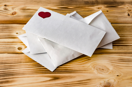 Happy Valentines Day. Postal envelopes with heart on a wooden background. Love. Celebratory background