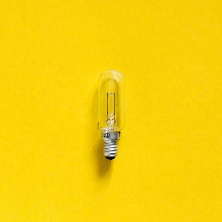Incandescence bulb over a yellow paper background. Tungsten glowing filament Stock Photo