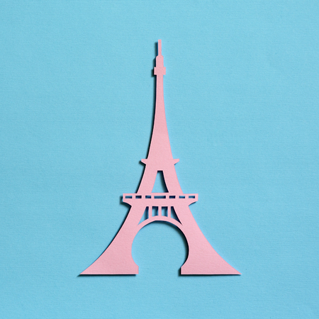 Cut from the paper Eiffel Tower on a turquoise textured background, top view. Flat lay