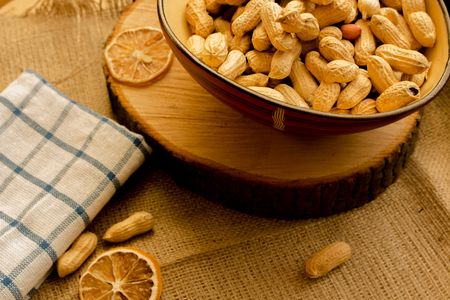 Peanuts and walnuts loose on canvas and in bowls. Stock Photo