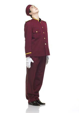 doorkeeper: Usher with red uniform stands straight and looks up to a presentation.