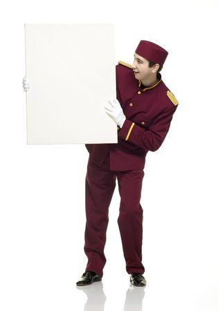acomodador: Usher con rojo uniforme sostiene un panel blanco.