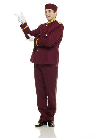 acomodador: Usher uniforme rojo con blanco y guantes de puntos en la presentaci�n.  Foto de archivo