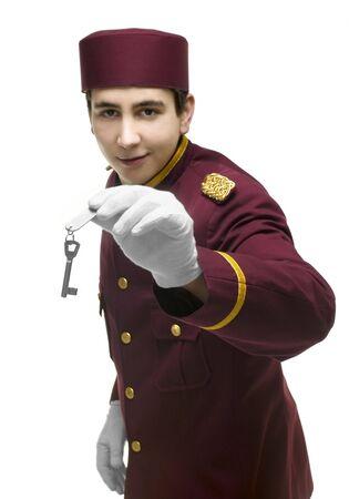 acomodador: Usher con uniforme rojo y guantes blancos presenta una clave incluida una etiqueta con una mano. FOCUS en mano y clave.