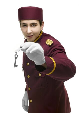 overseer: Usher with red uniform and white gloves presents a key including a label with one hand. FOCUS on hand and key.