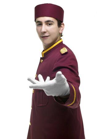 acomodador: Usher con uniforme rojo y guantes blancos presenta s.th. con un handgesture. ENFOQUE guante blanco.