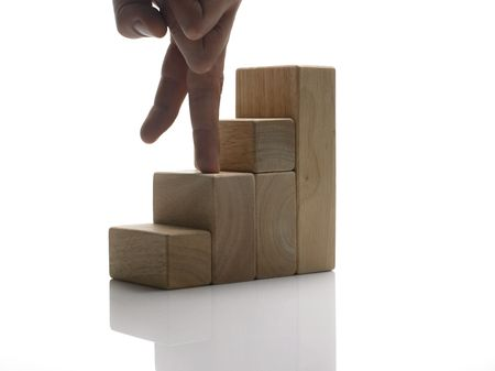 challange: Two fingers are climbing stairs made out of wooden toy blocks.