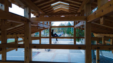 Person perched up in a wooden log farmers market structure.